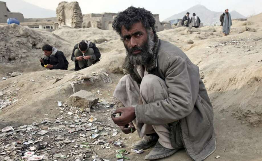 Addicts smoke heroin in a vacant lot in Kabul, Afghanistan, early this year. Up to one in every 25 Afghans was a heroin addict in 2005, according to the U.N. Office on Drugs and Crime.