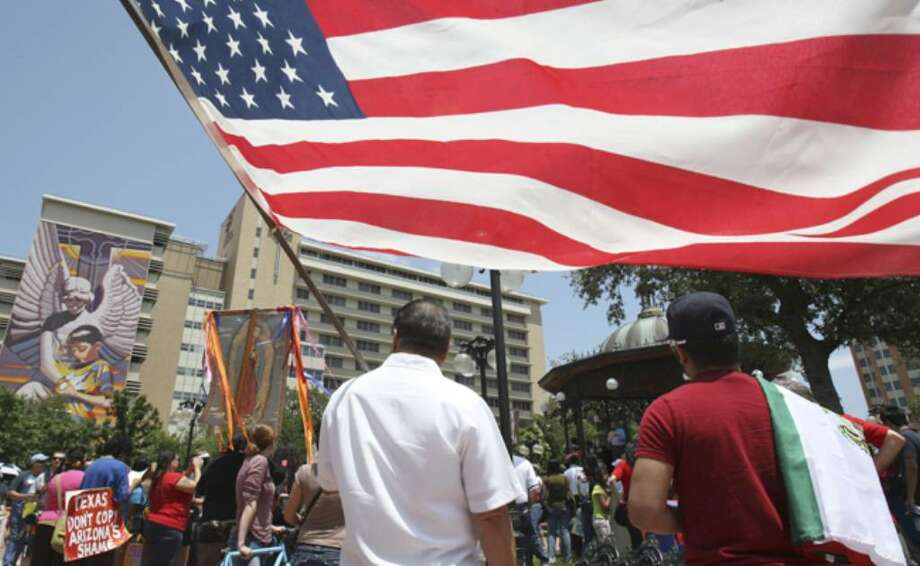 Catarino Aranda holds Old Glory while listening to the speakers in Milam Park before the march through downtown.