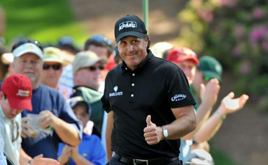 Phil Mickelson acknowledges the patron walking to the 6th green during the final round of the Masters golf tournament in Augusta, Ga., Sunday.