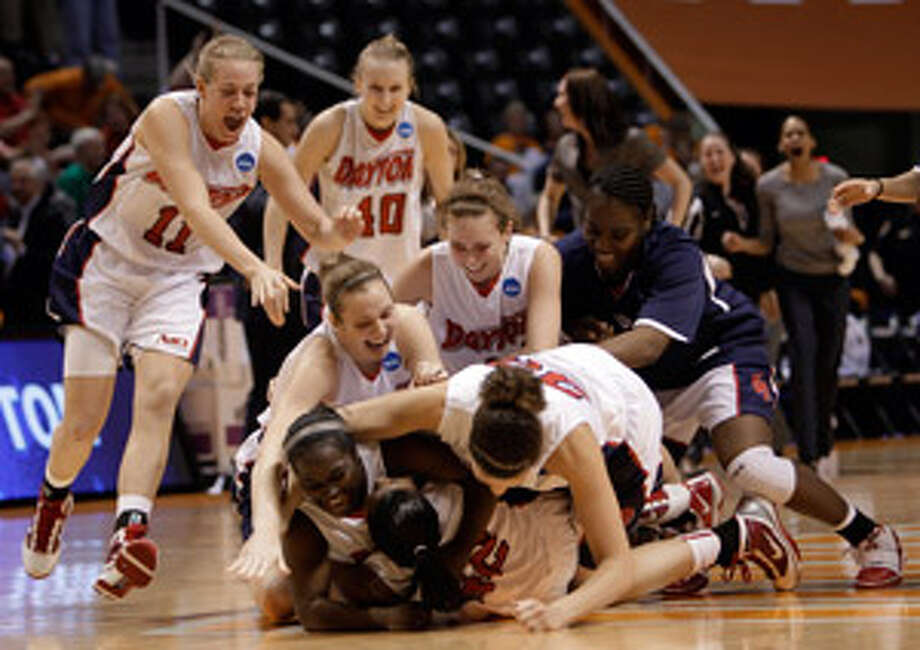 Dayton's Brittany Wilson (42, at bottom) is mobbed by teammates after her basket with 1.1 seconds remaining beat TCU. The Flyers advance to play Tennessee.