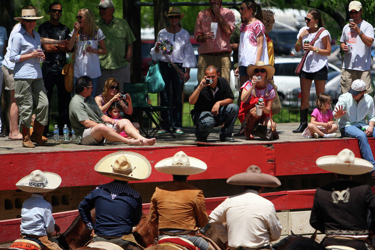 Charros circle the ring as spectators photograph them from the platform.