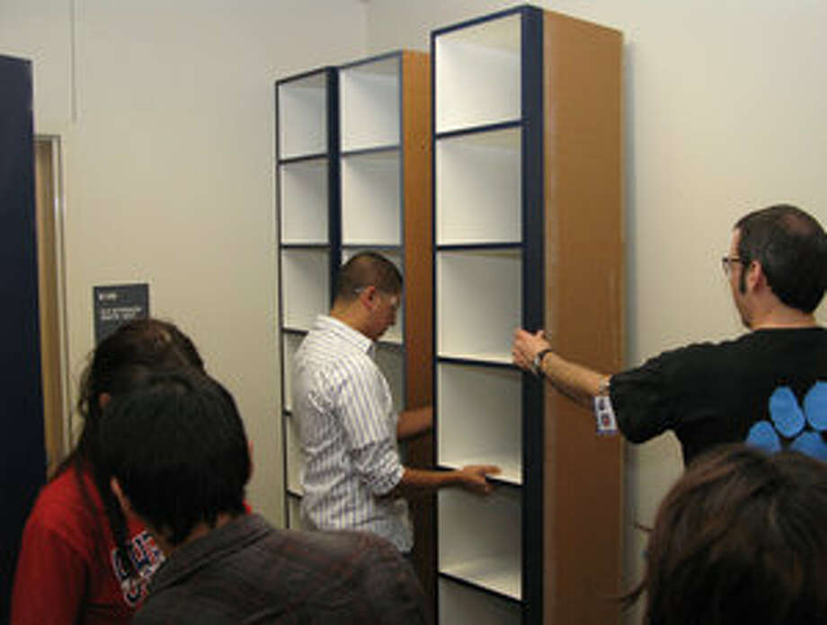 Conrad Antoon (right) supervises the work of the students in his mill and cabinetry class as they install cabinets in the Zamora Middle School library.