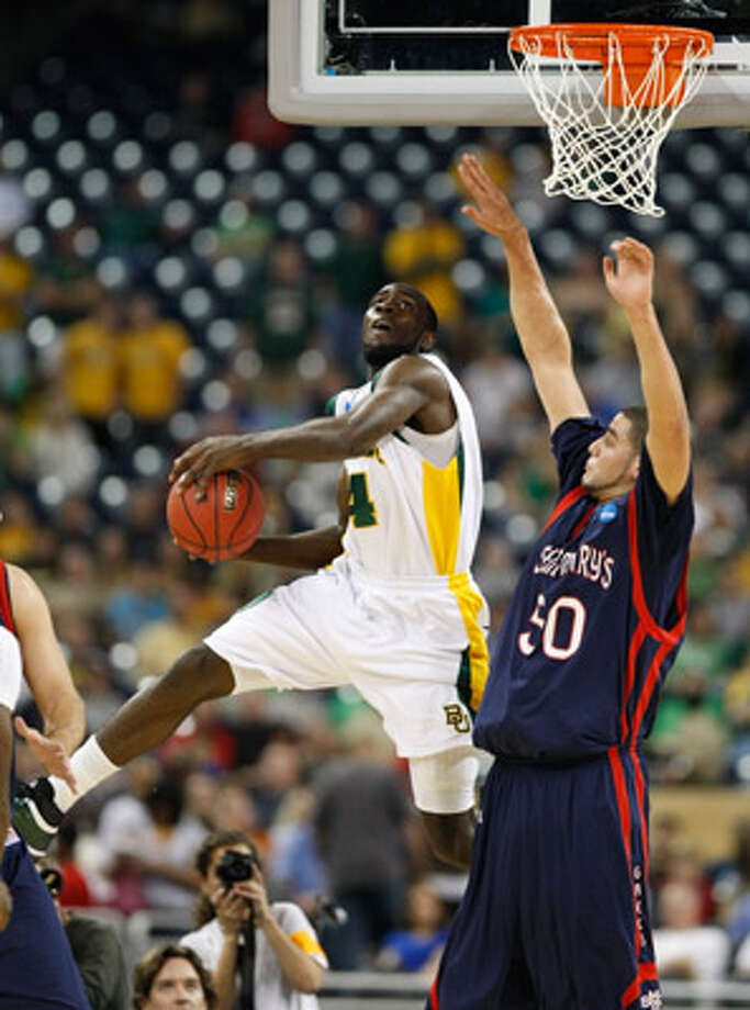 Baylor forward Quincy Acy goes up and over Saint Mary's center Omar Samhan during the first half.