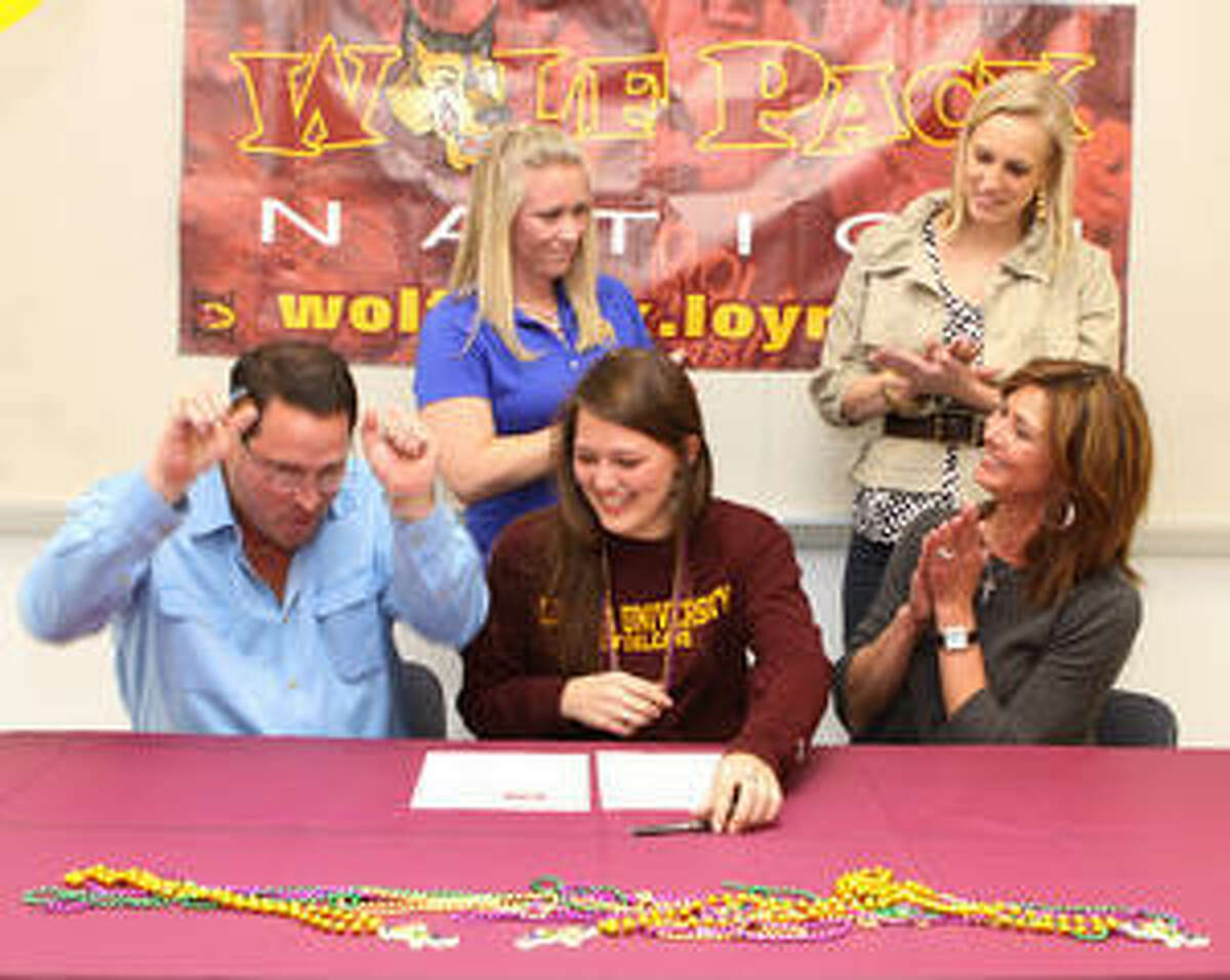 Alamo Heights High School's Shelby Plant (seated center) signs a volleyball scholarship to Loyola University in New Orleans, surrounded by (left to right) father Clint Plant, Mules volleyball coach Courtney Patton, volleyball club coach Shelly Vaughan and mother Sharon Plant.