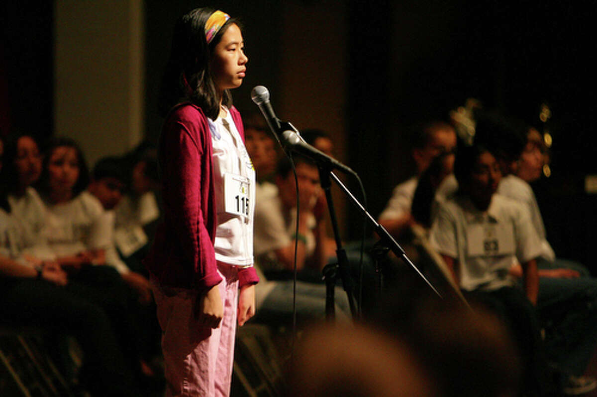 2nd place winner Katherine Mansfield, a student at Keystone School, spells a word in one of the early finalist rounds as her competitiors look on.