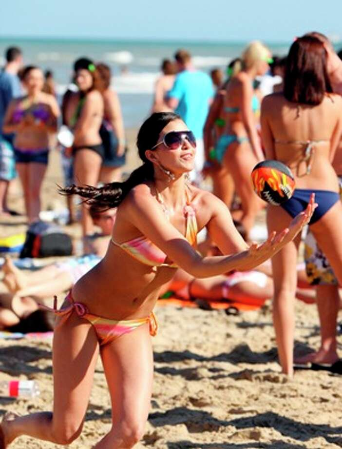 University of Texas-Pan American sophomore Celina De La Garza plays catch with friends Wednesday at Coca-Cola Beach on South Padre Island.