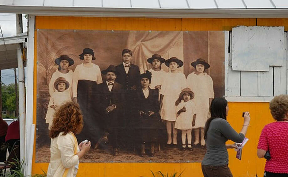Residents pass up one of many enlarged photographs lining Guadalupe Street during the recent Paseo Por El Westside, hosted by the Esperanza Peace and Justice Center.