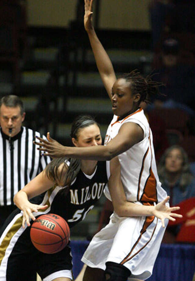 Missouri's Christine Flores, a former Churchill star, drives against Texas' Ashley Gayle during the first half. Flores had nine points and three blocks in the Tigers' loss to the Longhorns.