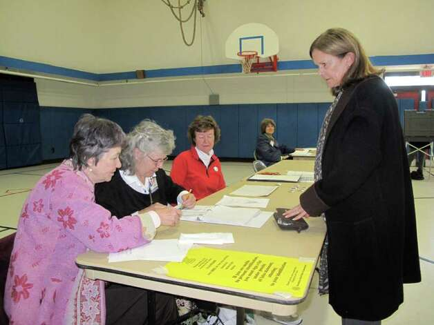 Robin Harvey of Darien registers for her turn to vote at the Ox Ridge School voting center Tuesday afternoon. By 2 p.m. officials said turnout was around 100 people per hour. Photo: File Photo / Darien News