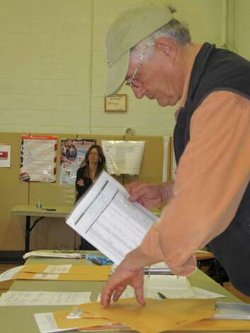 "Assistant Registrar of Voters Frank Kemp arranges paperwork at the Hindley School polling site Tuesday afternoon. He joked that the most important part of his job was to ""arrange to get lunch for the busy volunteers."" Photo: File Photo / Darien News"