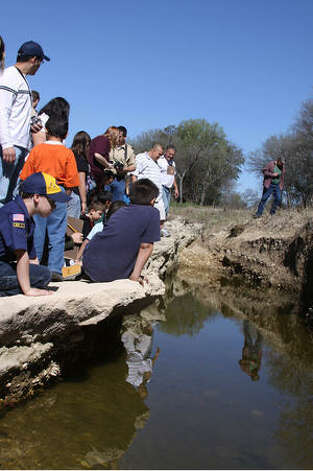 Cub Scouts from Pack 945 and their entourage explore along the creek bed in the 36-acre natural area behind the Huebner-Onion Homestead.