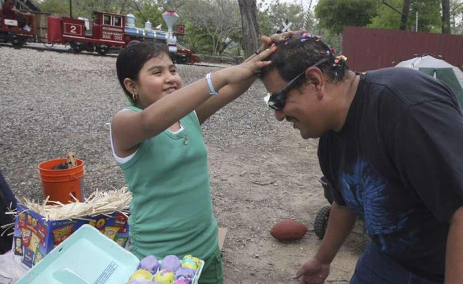 Brenda Gomez (left), 8, cracks a cascaron on her dad David Gomez's head on Easter Sunday at Brackenridge Park.