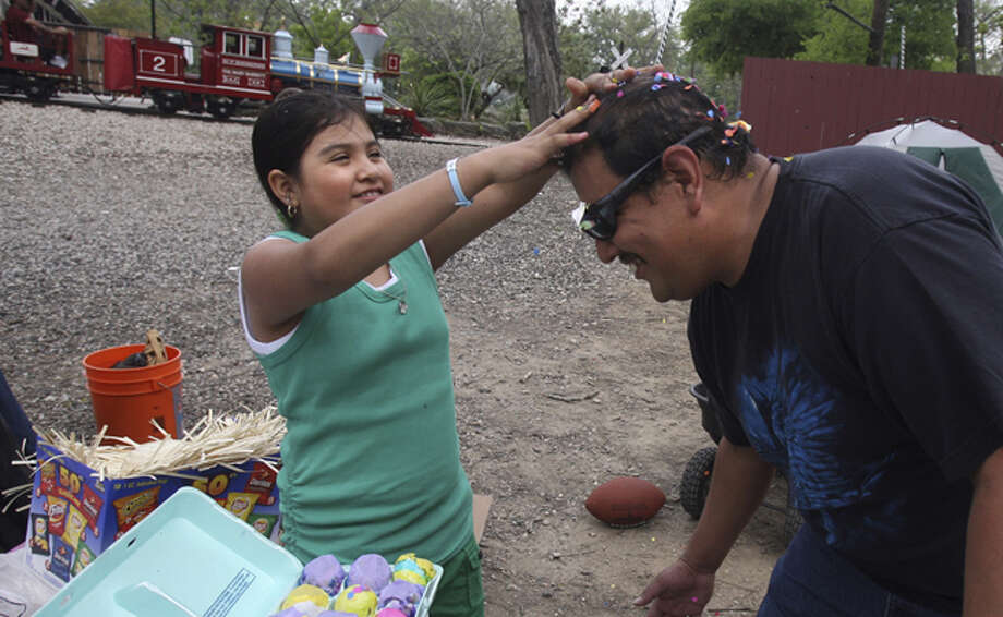 Brenda Gomez (left), 8, cracks a cascaron on her dad David Gomez's head on Easter Sunday at Brackenridge Park in 2010.