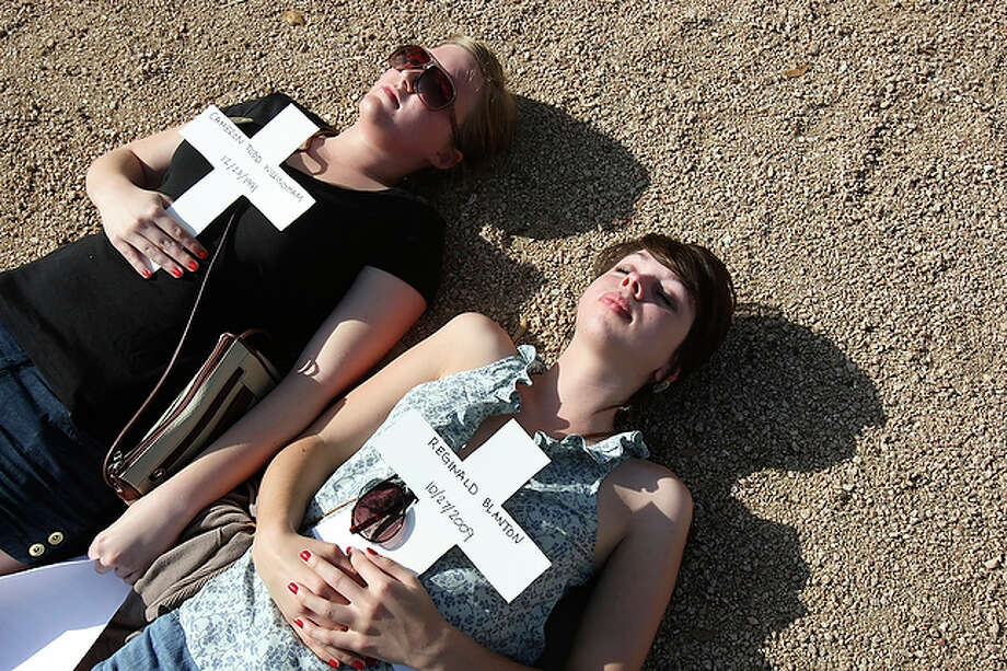 Friday, March 26 Michaela Wyatt and Hanna Campbell lie in the sand in Main Plaza after reading the final words of inmates who were executed.  The two were among the students who staged a protest in Main Plaza against the death penalty. Students read the final words of convicts who were given the death penalty and then laid on the ground in Main Plaza holding a cross baring the convicts name. / SAN ANTONIO EXPRESS-NEWS