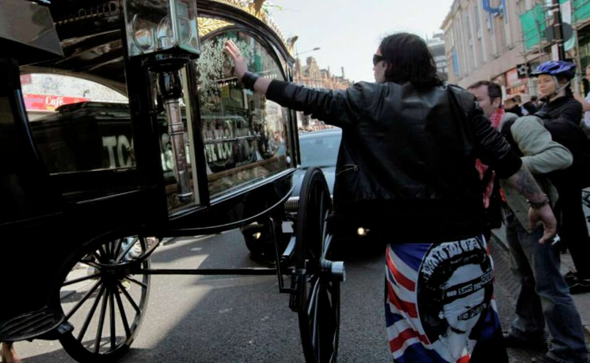 A man touch a hearse carrying the coffin of Malcom McLaren, music impresario, Sex Pistols manager and fashion guru, as it pass by London's Camden market during his funeral procession Thursday.