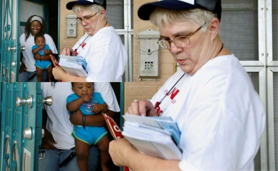 Census worker Sue Faifer speaks to Jasmine Lockett as she holds her 9-month-old daughter, Jordyn, at Wheatley Courts apartments on Saturday. Faifer and other census workers went door-to-door in an effort to get people to mail in their census forms.
