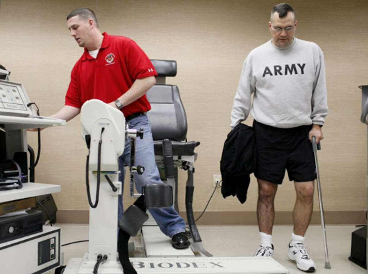 Sgt. Todd Plybon (right) works out with physical therapy assistant Mike Barber during physical therapy.
