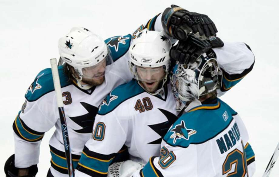San Jose players Douglas Murray (from left), Kent Huskins and Evgeni Nabokov celebrate their overtime victory over Detroit.