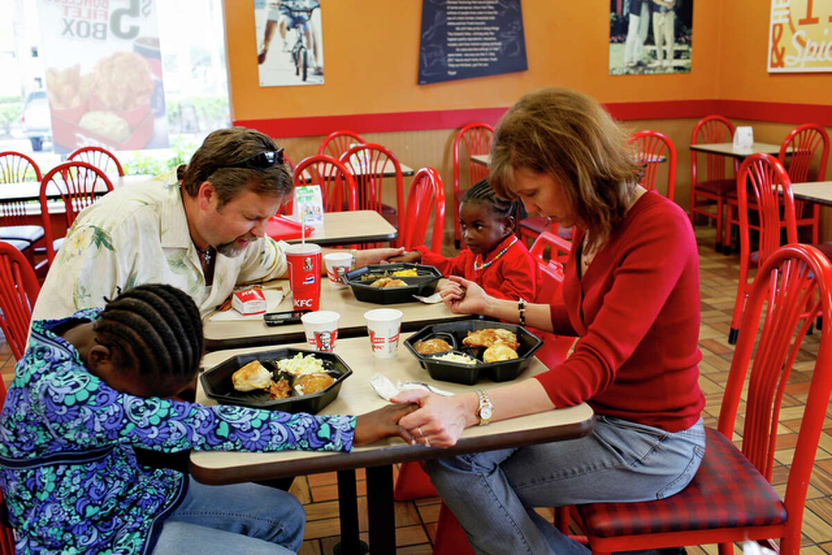 Lonise Jacques, age unknown, and Mikerlange Robert, known as Christelle, 13, left, pray with their adoptive parents, David and Laura Birdy, before their first meal in the United States at Kentucky Fried Chicken in Miami, FL on March 7, 2010.