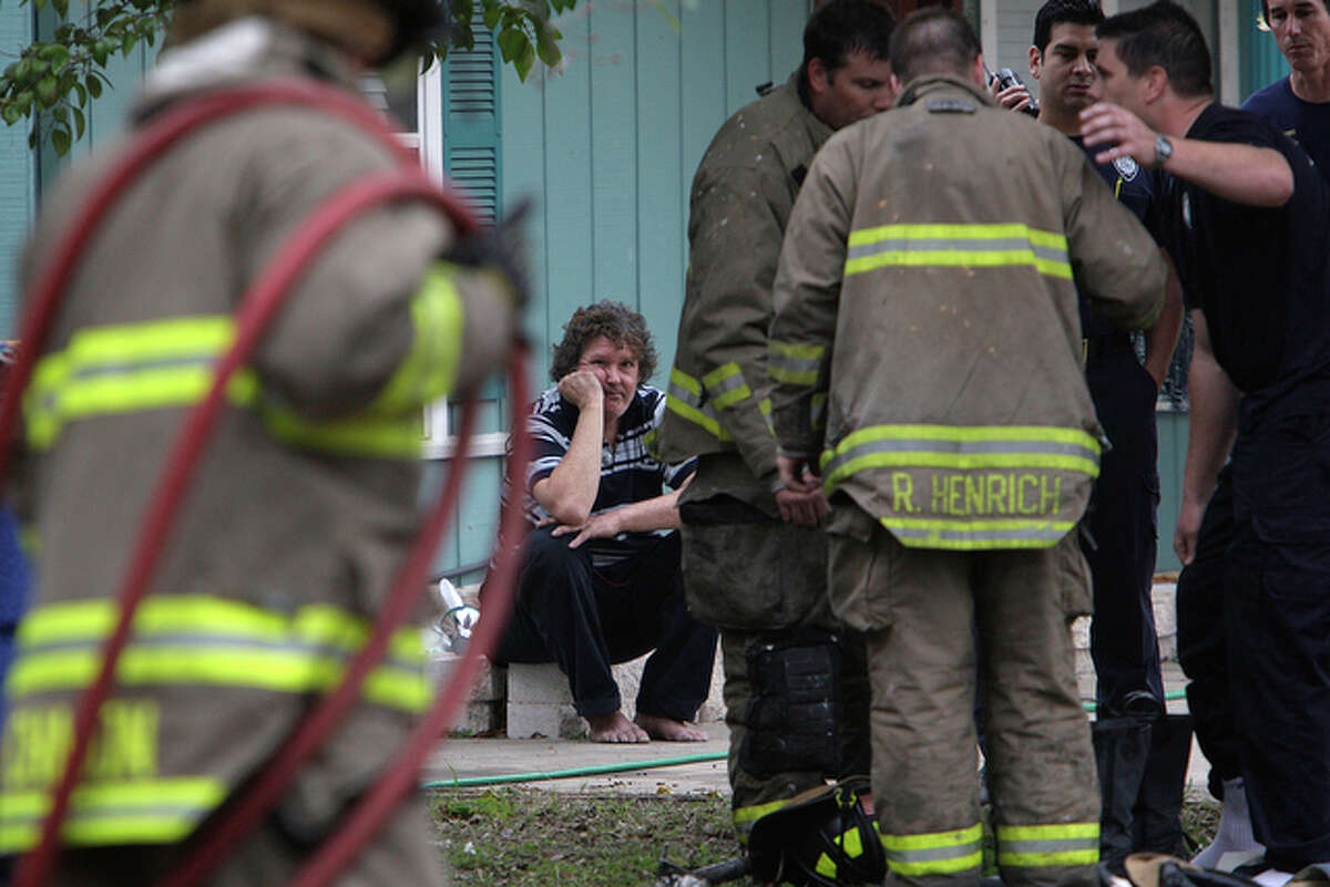 Daniel Dempsey, 50, waits in a neighbor's yard as San Antonio Fire Department work a structure fire at his home located at 8334 John Adams, Sunday, March 7, 2010. According to Battalion Chief Oscar Gonzalez, because the house didn?t have utilities, the fire was started by a candle placed on a windowsill close to curtains. The fire was contained to the one room but smoke damaged several other areas. One firefighter suffered minor injuries when he rolled his ankle exiting the house. Damange to the house was estimated at between $5,000-10,000.
