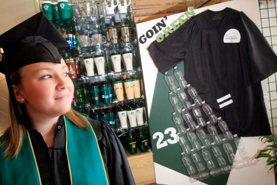"""University of Vermont bookstore employee and college freshman Nicole Walker, 19, models a graduation cap and gown made of recycled materials next to the store display showing that 23 water bottles equal one cap and gown in producing the graduation day attire. Academic apparel manufacturers are jumping into the market with """"green"""" options, ranging from disposable gowns that decompose quickly in soil to gowns made of recycled plastic bottles that can be reused or recycled."""