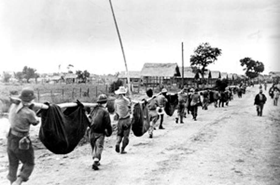 A photo released by the U.S. military in 1945, after it was captured from the Japanese, shows allied prisoners of war in the Philippines carrying their comrades in slings.