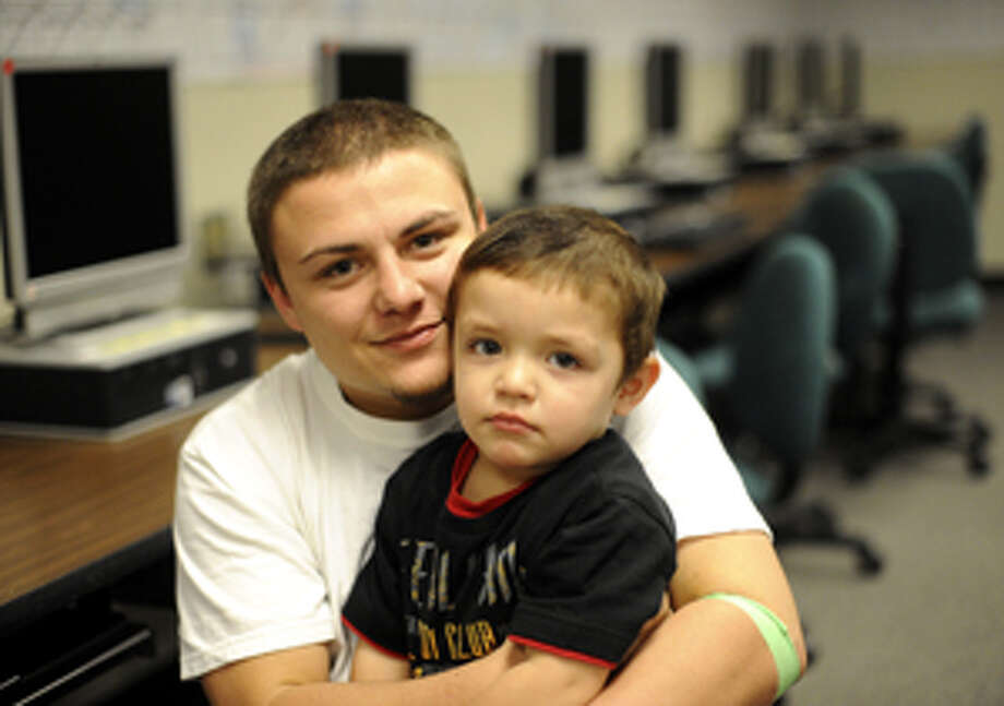 Teen father Jonathan Collier holds his 2-year-old son, Stephen, at the Judson Learning Center. ?I've always seen him as my gift, he came out looking just like me, he's like my mini-me. The last thing I'd want to do is get rid of him.?