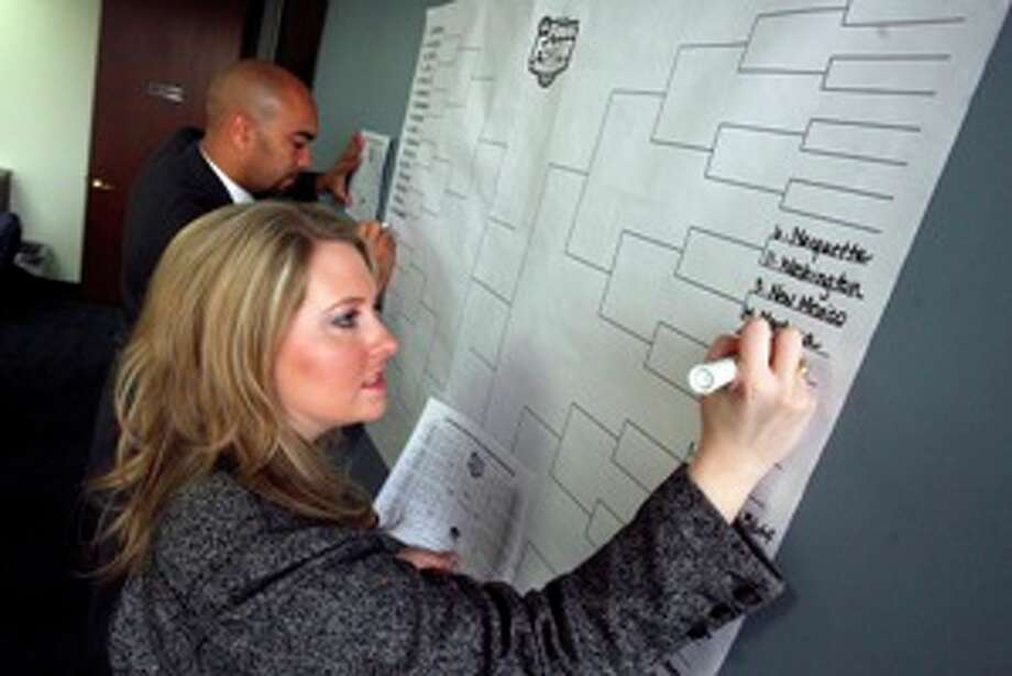 Whitney Bartle (front), a branch manager for Robert Half International, and Steven Robinson, a company branch manager for technology, fill in brackets for the NCAA men?s basketball tournament in one of the company?s offices.