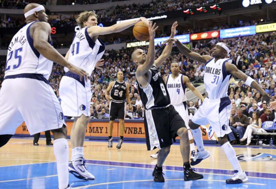 Spurs guard Tony Parker has his shot blocked by the Mavericks' Dirk Nowitzki as he drives into a crowd of Dallas players including Erick Dampier (25), Caron Butler (4) and Jason Terry (31) during Sunday's loss at American Airlines Center. Parker came off the bench to score 18 points and dish out four assists.