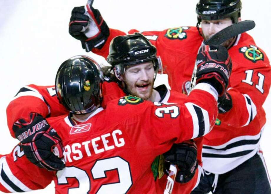Duncan Keith (center) celebrates with teammates Kris Versteeg (left) and John Madden.