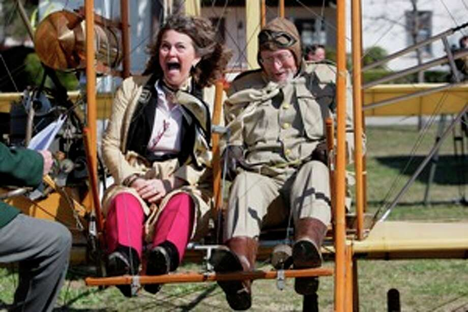 "Amanda Wright Lane, great grandniece of the Wright brothers,  takes a ride Tuesday on the Valentine Flyer-N, aka, ""The Yellow Bird,"" with pilot Don R. Gum, during the Fort Sam Houston celebration of the 100th anniversary of the first military flight by Lt. Benjamin F. Foulois."