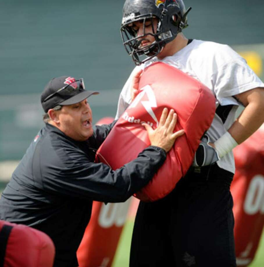 Incarnate Word offensive line coach and coordinator Tony Marciano instructs a lineman during Tuesday's practice.