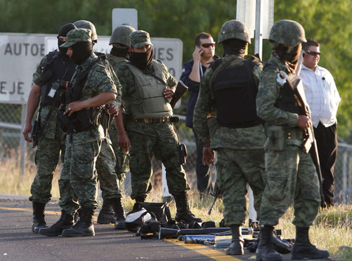 Mexican soldiers stand guard at the site of a firefight between drug traffickers and army troops on the outskirts of Monterrey.