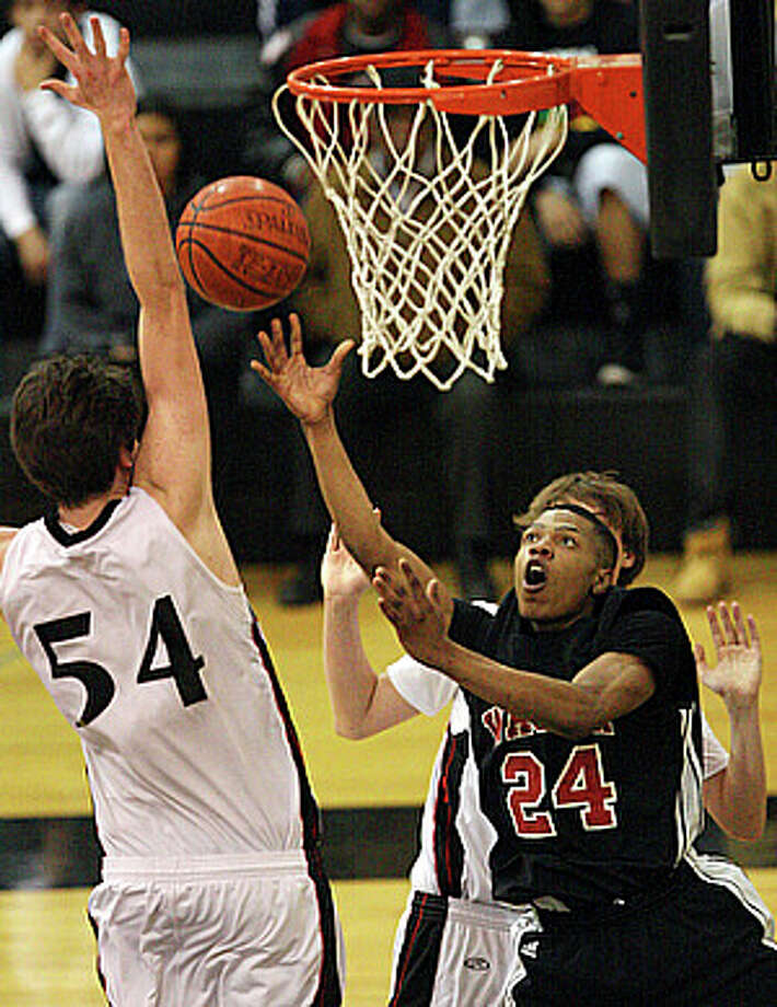 Wagner?s Devante Hill lays the ball up between Churchill?s Mike Byron (left) and Jacob Woods during the Thunderbirds? 88-69 victory in Seguin on Monday. / eaornelas@express-news.net