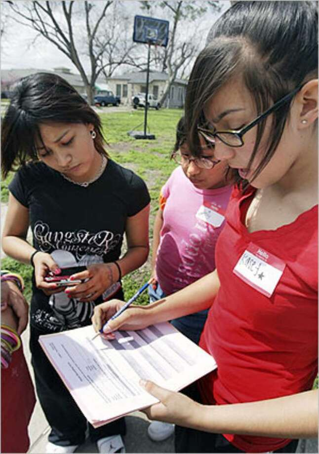 Emily Sanchez (center) watches Cassandra Delgado record data about the photograph of a basketball goal taken by Michelle Luis (left).