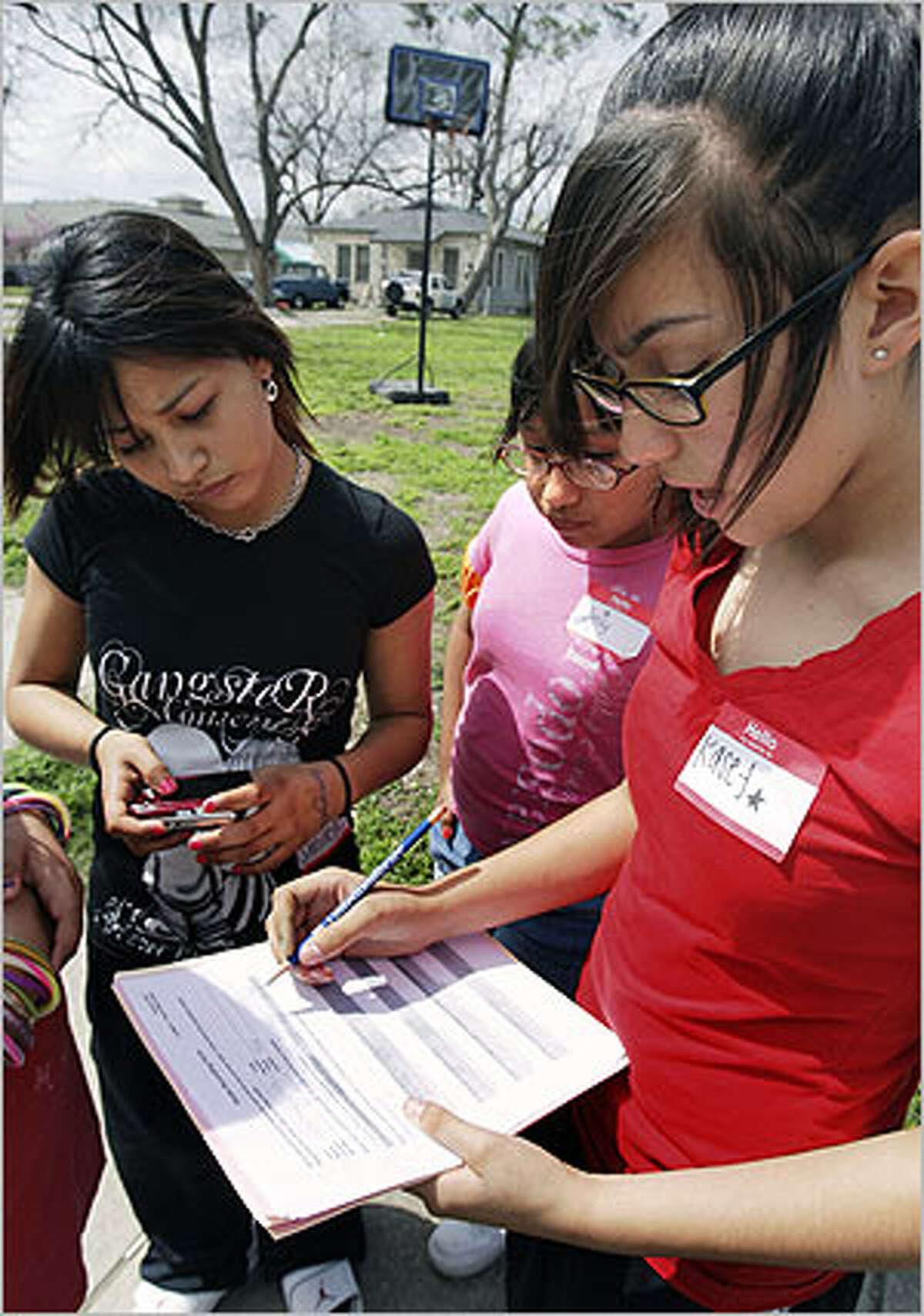 Emily Sanchez (center) watches Cassandra Delgado record data about the photograph of a basketball goal taken by Michelle Luis (left).