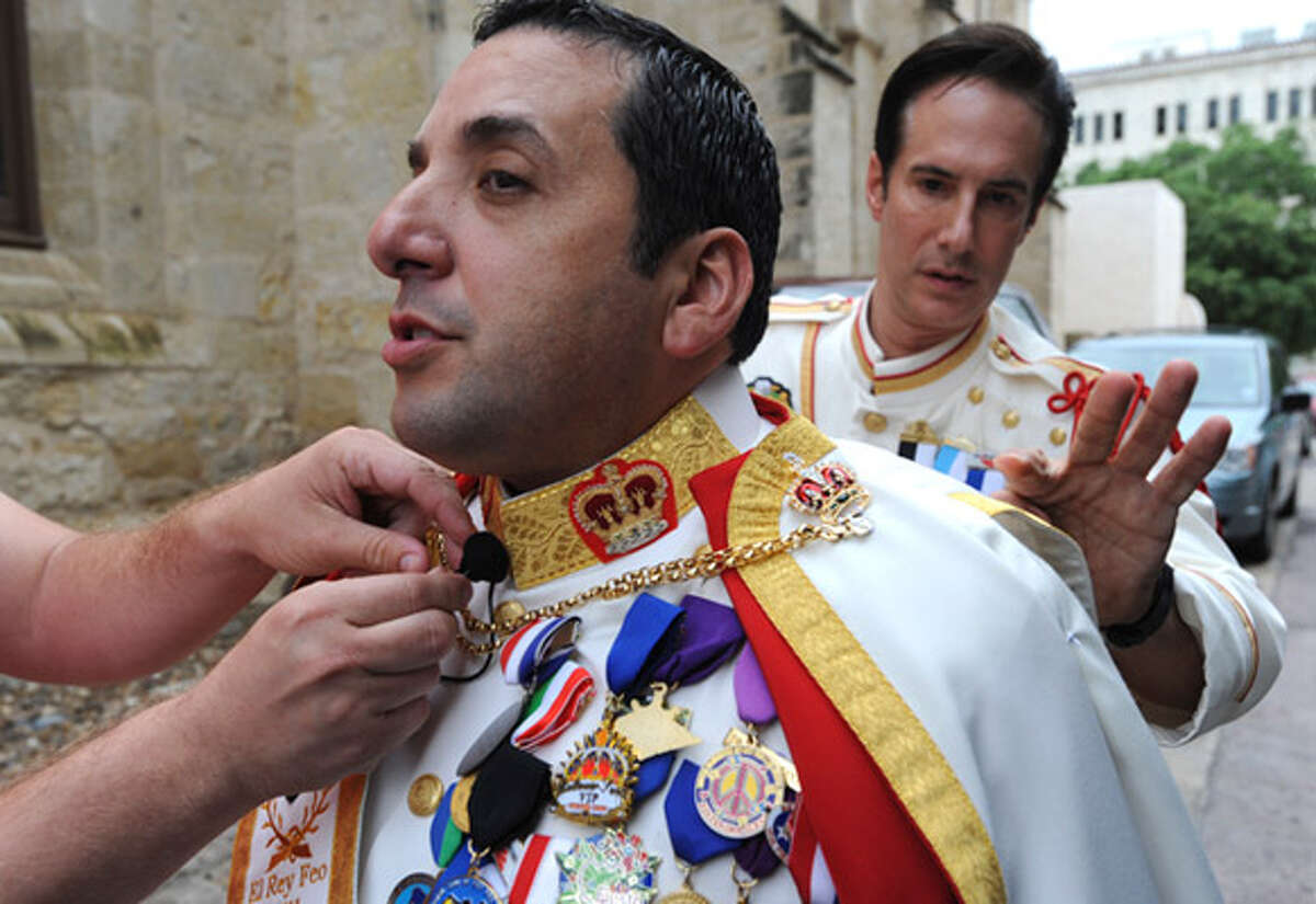 Baltazar ?Walter? Serna is wired with a microphone as his education minister, Dan Markson, helps him with his cape in preparation for his coronation as the 62nd El Rey Feo.