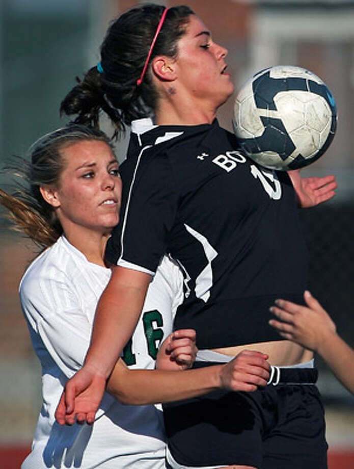 Reagan's Sarah Van Horn (left) is kept away from the ball by Austin Bowie's Jesse Traves during Tuesday's game.