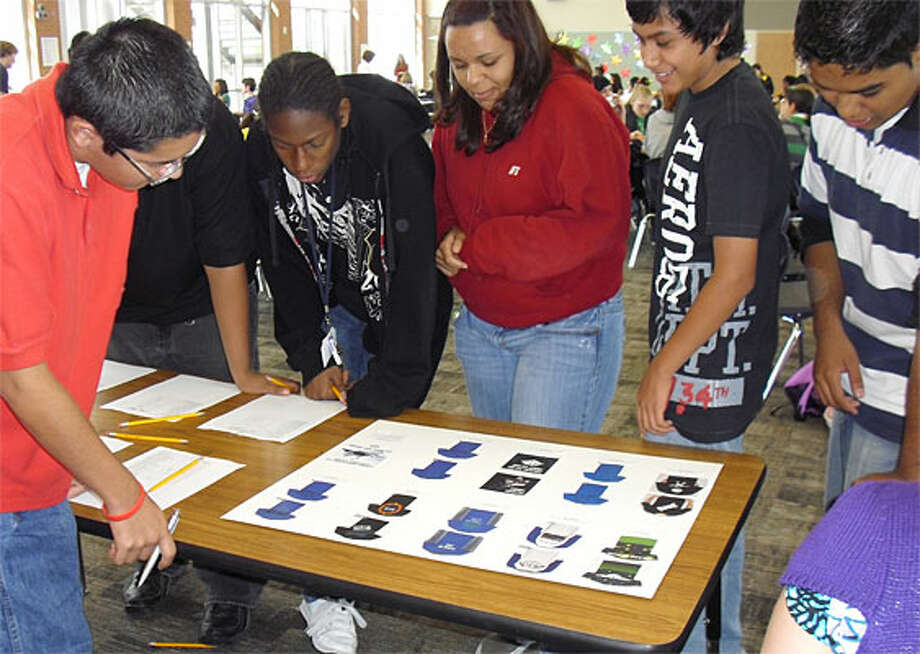 JECA students (clockwise from the left) Alfred Suarez, Kenneth Brown, Arianna Whittington, Jerry Guevara and Daniel Pina-Esparza are selecting their favorite student-created design in the JECA T-shirt contest. The winning designs were sold on T-shirts and hoodies for the Class of 2013.