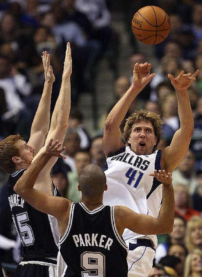 Mavericks forward Dirk Nowitzki passes out of a double team from the Spurs? Matt Bonner and Tony Parker.