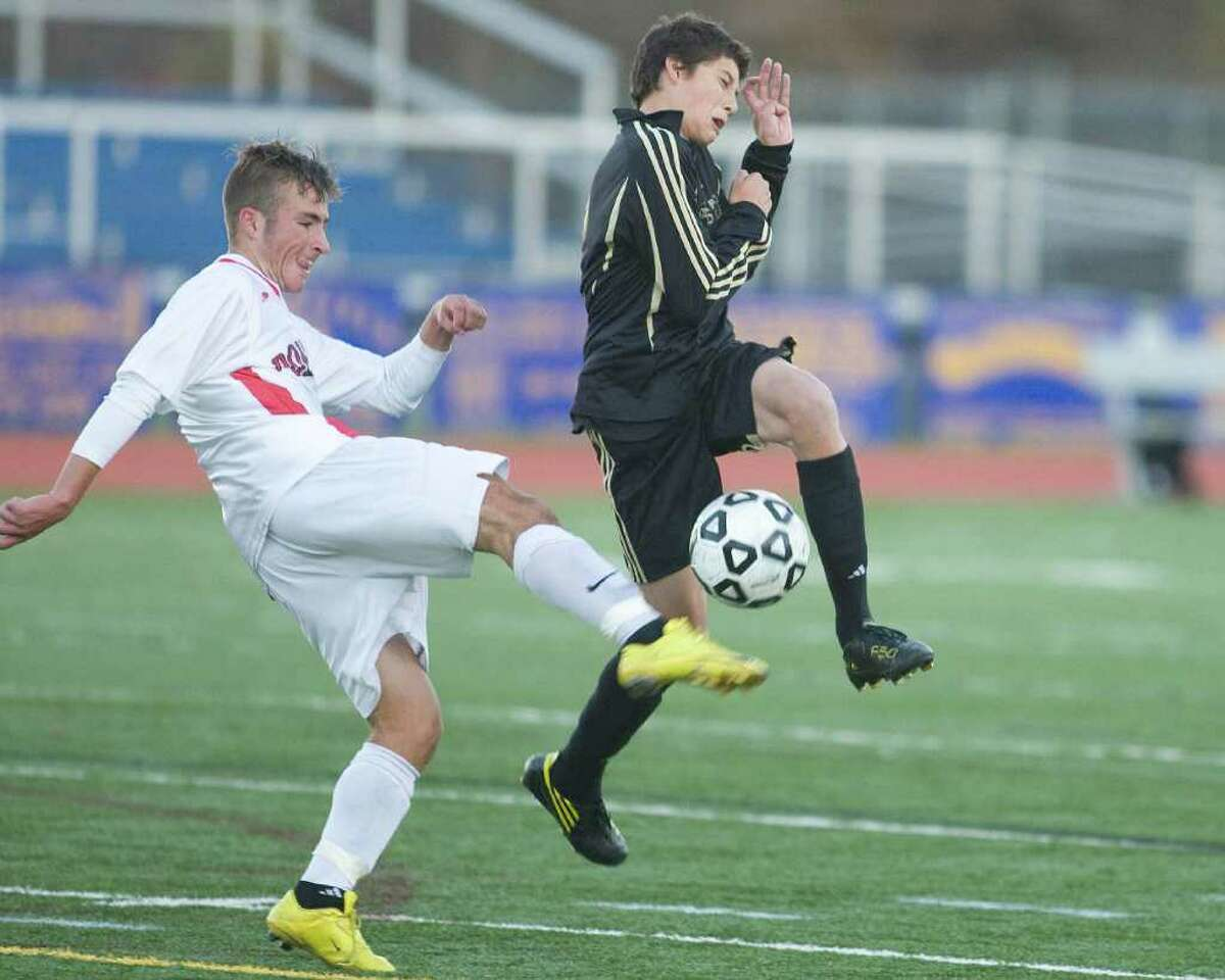 Pomperaug's Joshua Abromaitis, left, gets a pass off past a leaping Jeremy Nelle of Joel Barlow during their SWC tournament semifinal match Tuesday at Brookfield High.