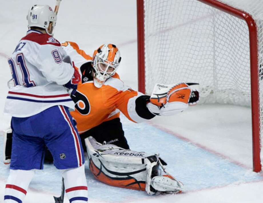 Flyers goalie Michael Leighton grabs the puck from the air in front of Canadiens center Scott Gomez during a power-play attack in the third period of Game 2. The Flyers won 3-0 for a two-game lead.