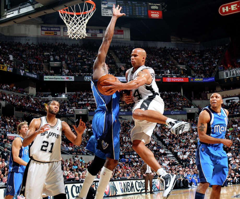 Spurs' Richard Jefferson passes around Mavericks' Erick Dampier to teammate Spurs' Tim Duncan. / © 2010 SAN ANTONIO EXPRESS-NEWS