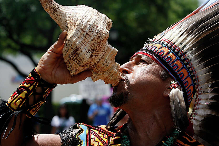 Kuauhtli Vasquez blows into a conch shell during a march protesting Senate Bill 1070 proposed in Arizona on a route between Milam Park and the San Fernando Cathedral on Saturday, May 1, 2010. / mmiller@express-news.net