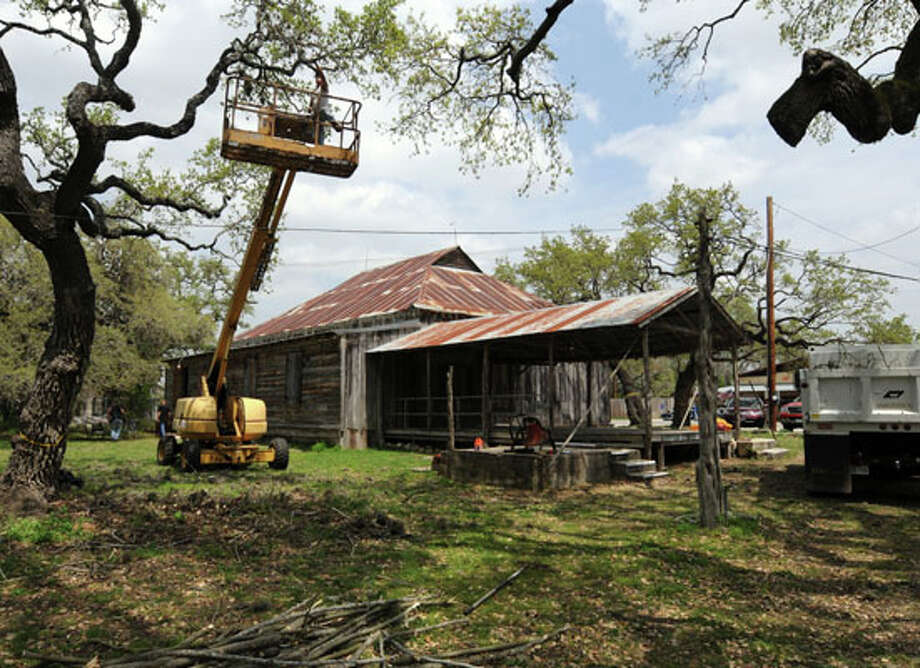 A workman trims trees in the back of the Sisterdale Dance Hall and community Center as part of its' redevelopment and preservation. The effort to the 100 year old plus facility is being headed by San Antonio attorney Wayne Wright. / Robert Jerstad