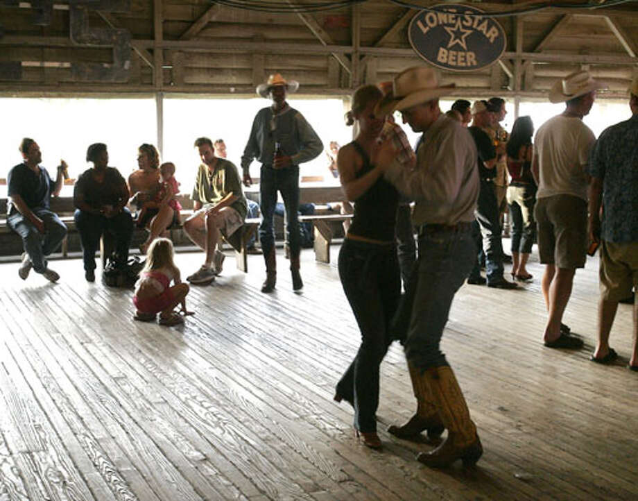 Couples spin around the dance floor as the South Austin Jug Band plays at Gruene Hall May 7, 2006. / Dallas Morning News