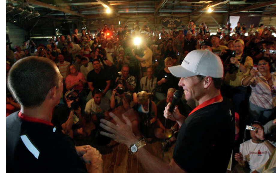 Lance Armstrong, right, and to his partner in the Tour de Gruene, John Korioth, at the awards ceremony in Gruene Hall. Armstrong won the race with a time of 56:31. / jdavenport@express-news.net