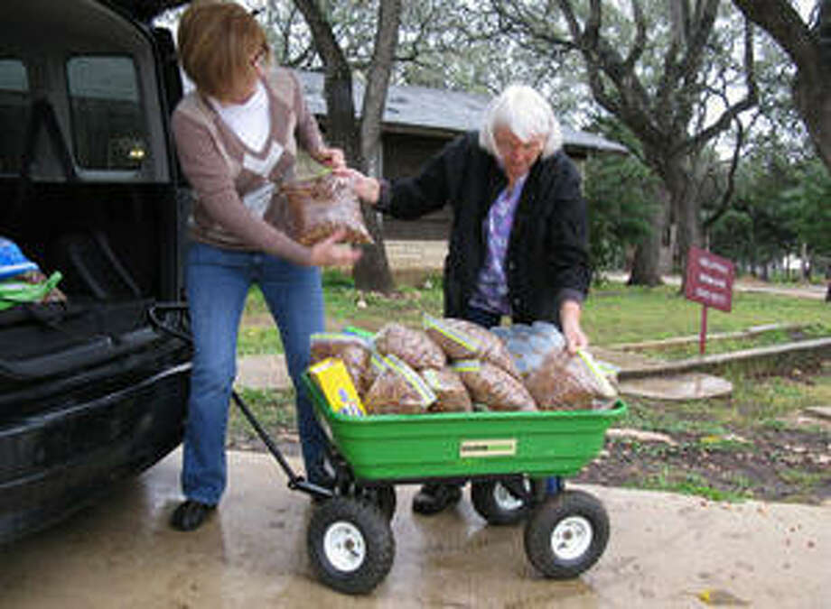 Helotes Humane Society volunteers Lois Tanigawa (right) and Stephanie Dunlea pack up pet food at the organization's pet food bank on Bandera Road for distribution to needy pet owners.