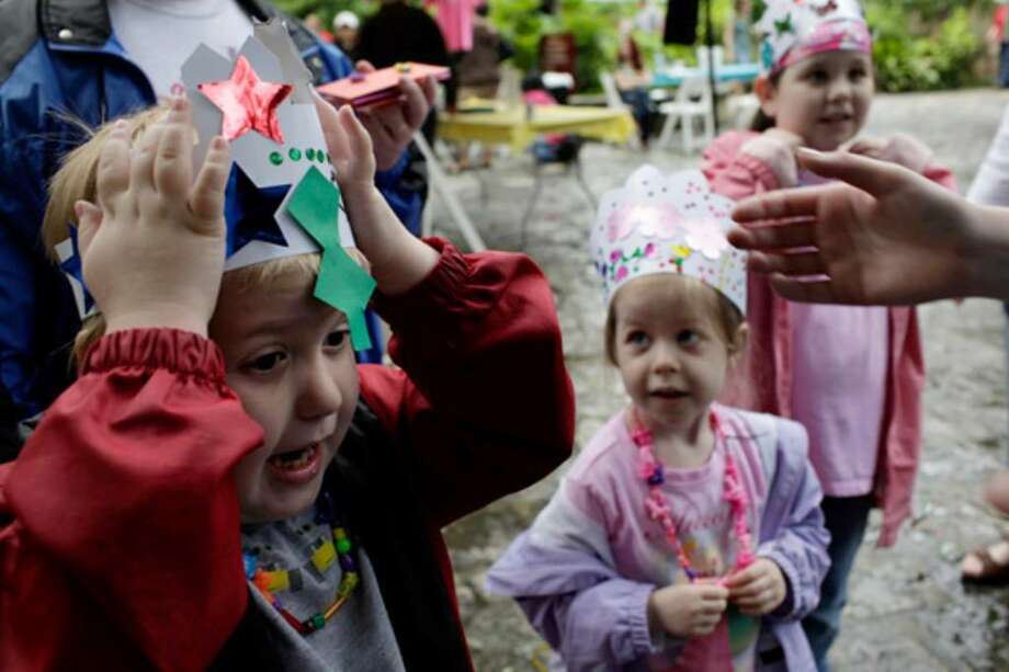 Quade Curtis, 7 (from left), reacts to the crown he made being too tight as his sisters Emerson Curtis, 5, and Makenna Curtis, 9, look on after they made crowns and necklaces in the Children's Art Garden during the Fiesta Arts Fair at Southwest School of Art & Craft.