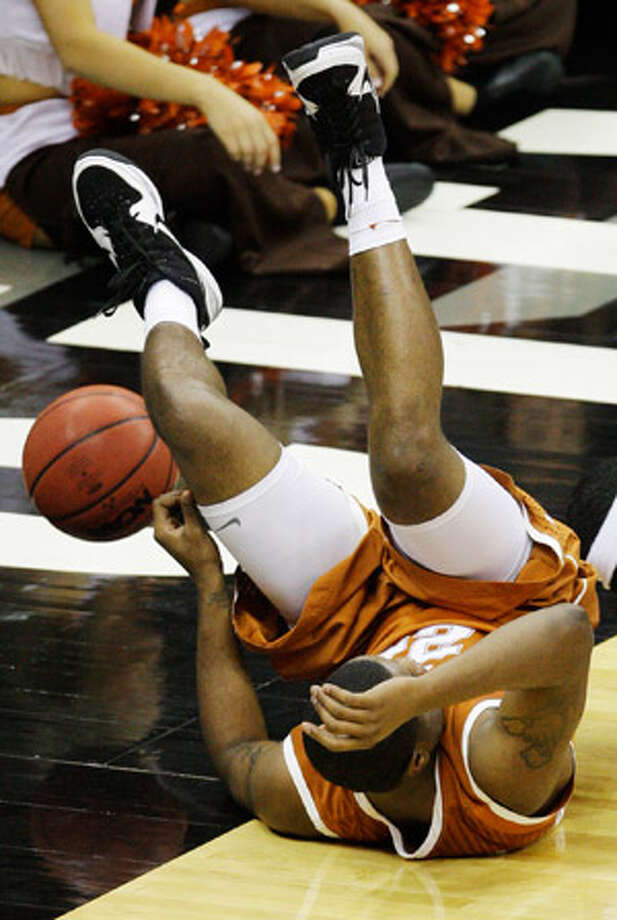 Texas guard Justin Mason falls with a rebound during the Horns? 86-67 loss. Mason scored nine points.